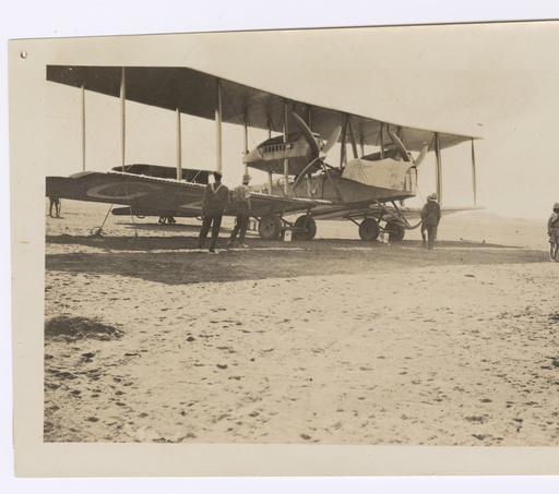 Image: Biplane on flat desert landscape. Tent off in the distance with armed guards.