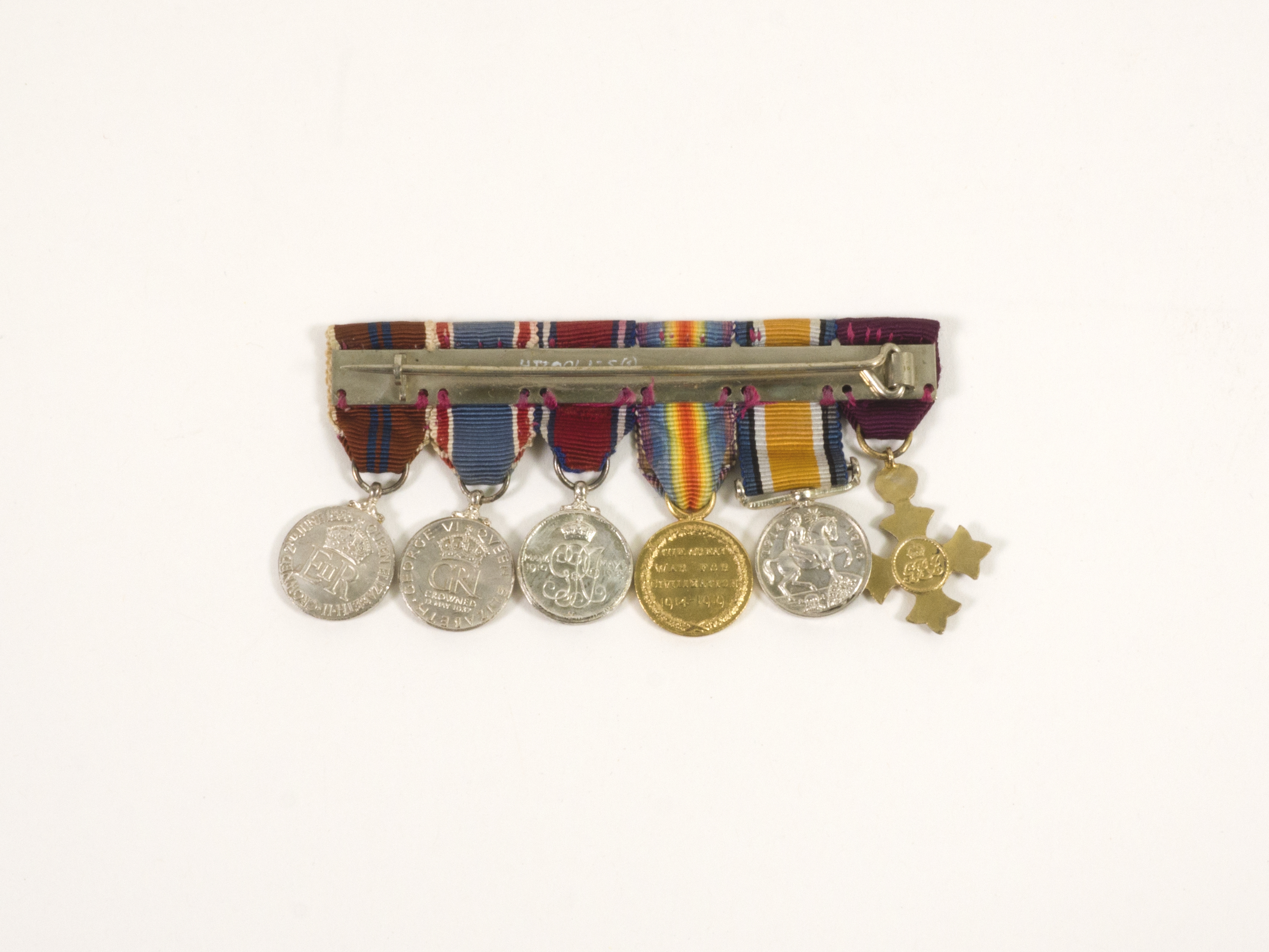 Image: six medals and ribbons aligned together and shown from the back side. Medals are attached to a metal clasp and pin to adorn on clothing. Five of the medals are circular and the sixth is shaped as a cross with a circular middle.